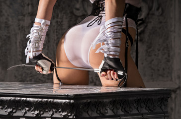 Woman with beautiful ass in white lingerie with a whip