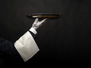 Waiter hand holding tray over black background.