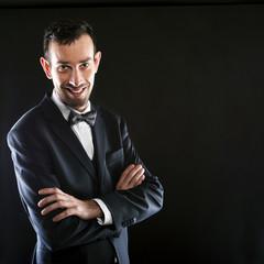 Portrait of handsome stylish man in elegant black suit.