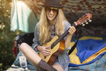Portrait of young woman playing ukulele whilst camping in pick up boot