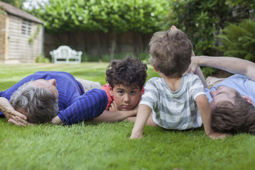 Three generation family fooling around in garden