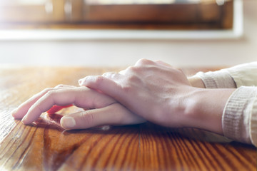Close-up of woman hands in reflexive and relaxing position on wooden table