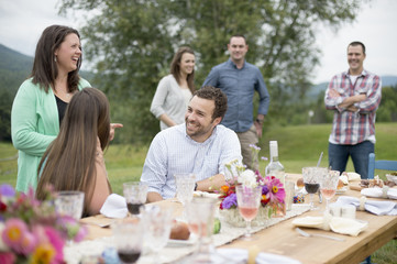 Family and friends gathered around, talking, at the end of a meal, outdoors