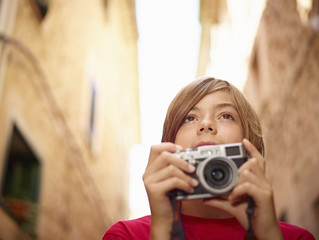 Close up of boy photographing village street using SLR camera, Majorca, Spain