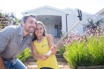 Father and daughter taking a selfie with selfie stick