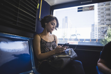 Young woman commuting on bus listening to music on smartphone, New York, US