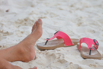 Young girl legs and flip-flop on the sand beach