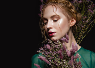 Beautiful girl with a gentle make-up, hairstyle  in the form of braids,  dry flowers, green dress. Beauty face.