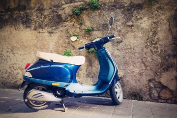 one motor scooter closeup against a stone wall
