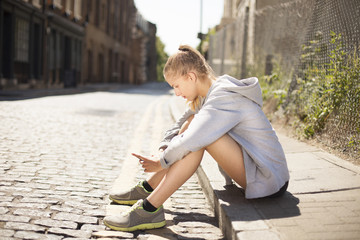 Runner using smartphone on pavement, Wapping, London