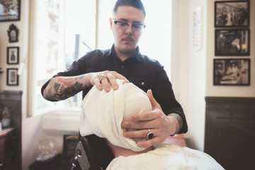 Barber wrapping towel around clients face in barber shop