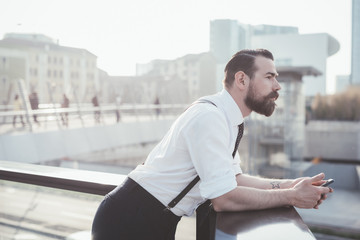 Stylish businessman with smartphone looking out from office balcony