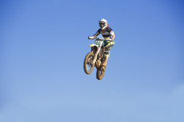Young male motocross racer jumping mid air against blue sky