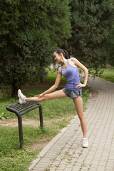 Young female runner stretching legs on park bench