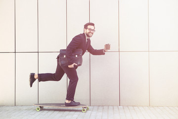 Toned picture of confident businessman smiling for camera and going to his office on longboard. Freelance man holding cup of coffee.