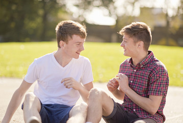 Two young male friends chatting in park