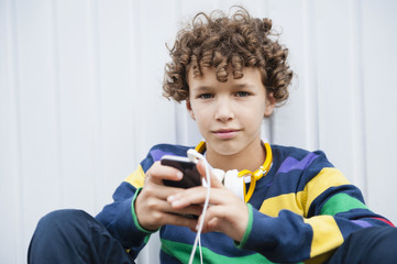 Portrait of confident boy sitting leaning against wall with headphones and smartphone