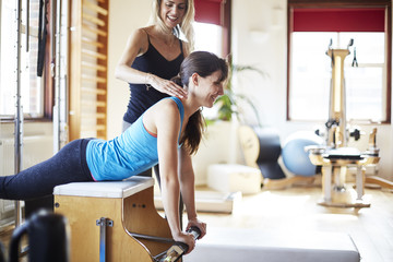 Young female student pushing up from combo chair in pilates gym