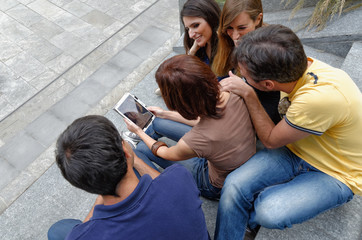 Group of friends looking at digital tablet, rear view