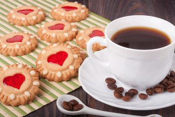 coffee cup with beans and cookies on the wooden table
