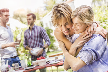 Group of friends setting up garden party, two female friends embracing