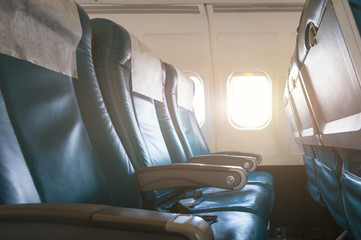 Empty aircraft seats and windows with sun light