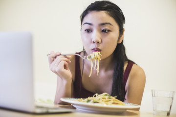 Young woman at table eating plate of noodles