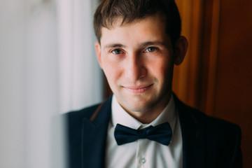 Handsome brunette man in blue bow tie posing near window, groom morning preparing