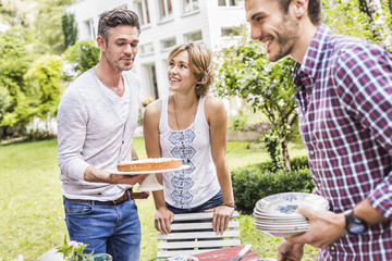 Group of friends setting up garden party, mid adult man carrying cake