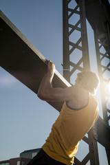 Man doing chin ups on bridge, Munich, Bavaria, Germany