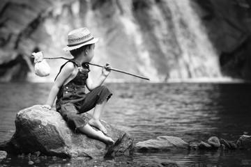 Abenteuer eines kleinen Jungen der am Wasserfall auf einem Stein sitzt und einen Strohhut, zerrissene Jeans und ein Bündel trägt