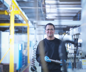 Portrait of engineer holding part in factory