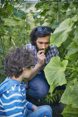 Father and son smelling plants on allotment