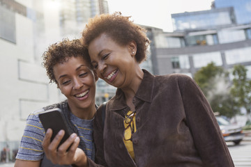 Two mature female friends laughing at smartphone texts on street