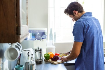 Man chopping vegetables at kitchen counter