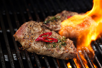pork steak on bbq grill with flame