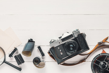 Retro camera, old photo film rolls, empty photos and magnifier