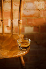 espresso coffee in clear glass cup on vintage chair with old bri