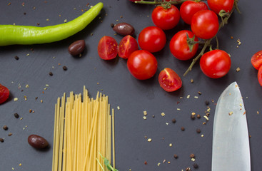 Pasta, cherry tomatoes and green pepper on black background