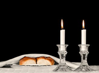 Shabbat candles in glass candlesticks isolated, covered challah bread background