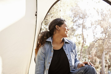 Young woman looking from tent entrance