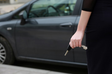 female hand holding  car keys. Back view. female driver standing in front car, outdoors