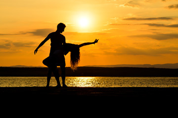 Couple silhouette dancing by the sea at sunset