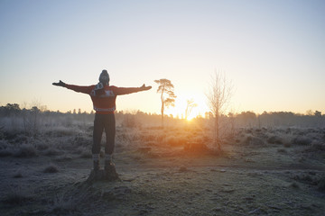Man with arms open in sunlit rural winter scene