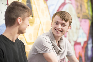 Teenagers relaxing against wall with graffiti