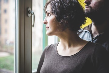 Couple standing together, looking out of window