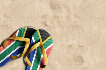 Thongs with flag of South Africa, on beach sand