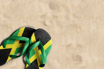 Thongs with flag of Jamaica, on beach sand