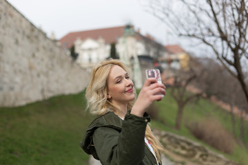 Girl with smart phone taking photo of herself. Budapest