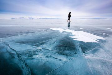 Girl photographer walking on cracked ice of a frozen lake Baikal